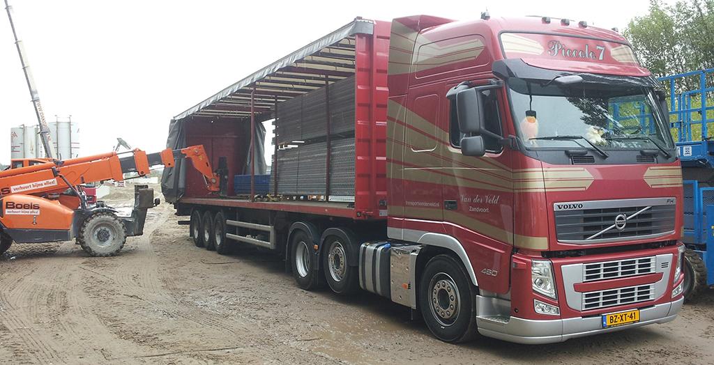 vrachtwagen Transport Van der Veld wordt gelost op een bouwplaats door een verreiker